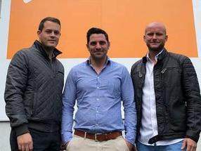Foto von links: Dominik Kagerer, Tobias Löwe und Sebastian Czaplicki. (Im Hintergrund das orangene Banner befindet sich auf der Hauswand des IGZ.)