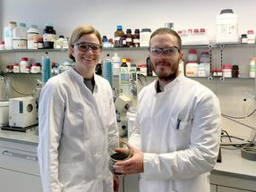 Corinna Dawid and Christoph Hald presenting a glass beaker with rapeseed in their laboratory.