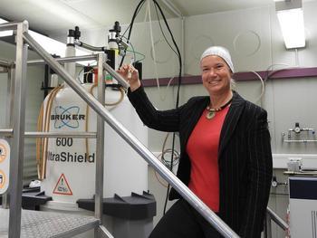 Prof. Dr. Ruth M. Gschwind, wie sie ein NMR-Röhrchen mit Ionenpaaren in das Spektrometer gibt