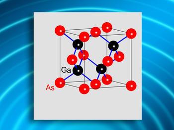 Elementarzelle von Galliumarsenid (Würfel mit einer Kantenlänge von 0,56 nm [ein millionstel von 0,56 mm]) mit Galliumatomen (schwarz) und Arsenatomen (rot), die durch kovalente Bindungen (blau) zusammengehalten werden. Ein Galliumarsenidkristall besteht aus vielen Milliarden solcher Einheitszellen.
