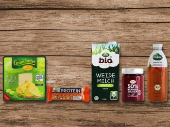 """Welches Produkt aus dem Supermarkt ist die dreisteste Werbelüge des Jahres? Darüber können Verbraucherinnen und Verbraucher bis zum 6. September abstimmen. foodwatch hat fünf Kandidaten nominiert: den Grünländer Käse von Hochland, den Be-Kind Proteinriegel von Mars, die haltbare Weidemilch von Arla, den Fruchtaufstrich """"50 % weniger Zucker"""" von Zentis und den Volvic Bio Roiboos Tee von Danone Waters."""